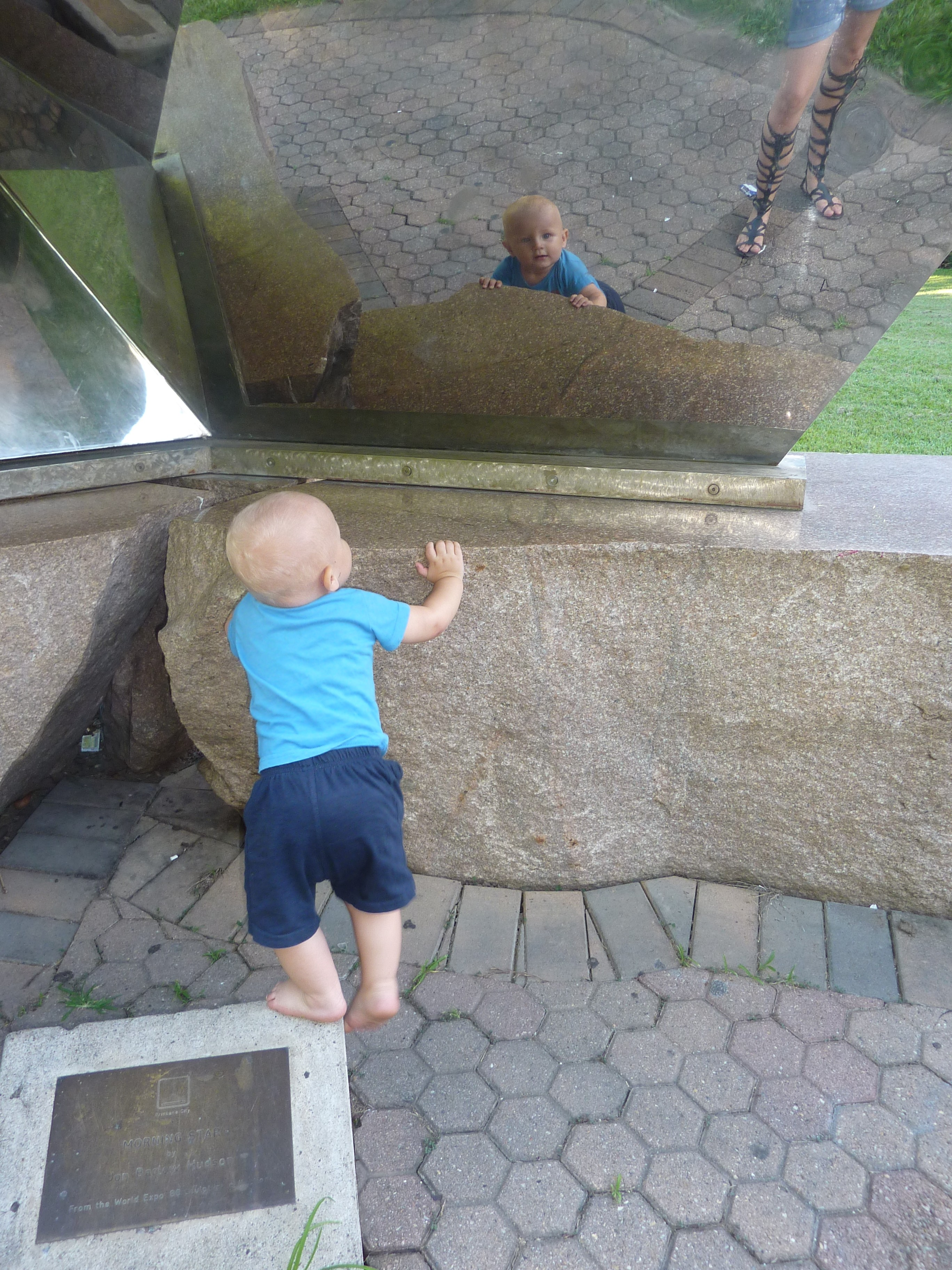 Xander looks at his reflection in the Morning Star sculpture